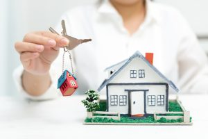 Choosing Real Estate Agent 300x200 - Real estate agent with house model and keys