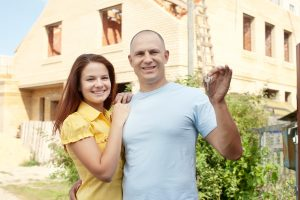 Happy Couple Holding House Keys 300x200 - Happy couple against building new house