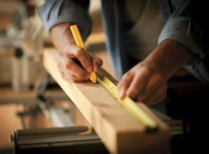 Website Carpenter 300x221 - Man Measuring Board